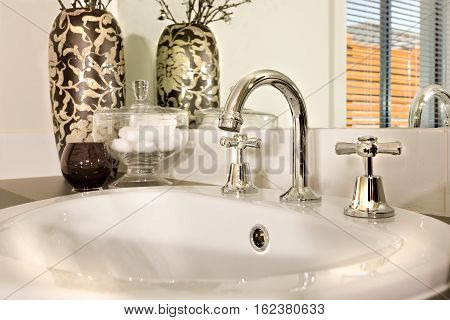Modern sink and a faucet closeup view next to the glass with a vase decorated with vines beside to a glass bowl The sink is shiny white made of ceramic and the tap is curved and made in silver steel and a mirror behind the countertop