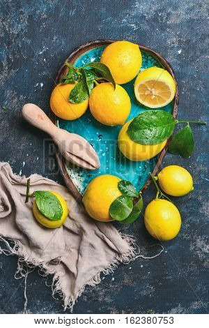 Freshly picked lemons with leaves in blue ceramic plate over dark blue shabby plywood background, top view, vertical composition