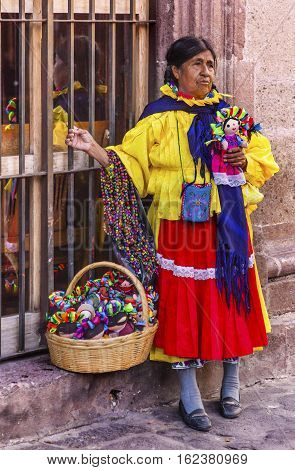 SAN MIGUEL DE ALLENDE, MEXICO - DECEMBER 27, 2014 Indian Woman Peddler Souvenires Lupita Dolls Jardin Town Square San Miguel de Allende Mexico.