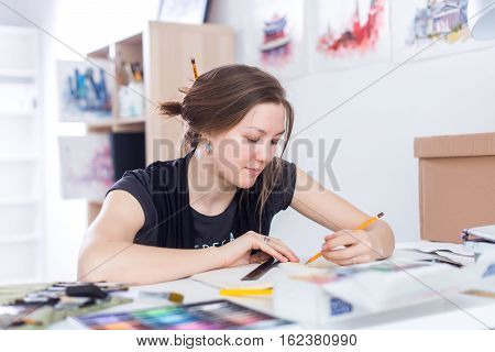Young female artist drawing sketch using sketchbook with pencil at her workplace in studio. Side view portrait of inspired painter