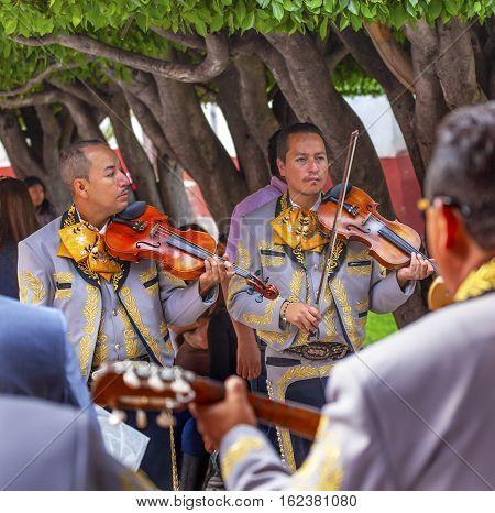 SAN MIGUEL DE ALLENDE, MEXICO - DECEMBER 27, 2014 Mariachi Band Violin Players Jardin Town Square San Miguel de Allende Mexico.