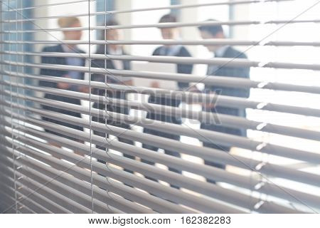 Four working busnesspeople viewed through jalousie in office