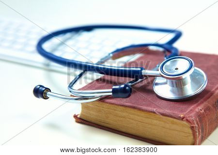 Medical stethoscope with old books and laptop on a table.