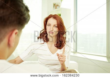 Young woman complaining to her husband at home