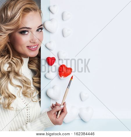 Young happy woman painting in red decorative hearts, Valentines day concept