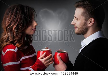Young couple holding coffee mags with heart shaped steam, Valentine's day concept