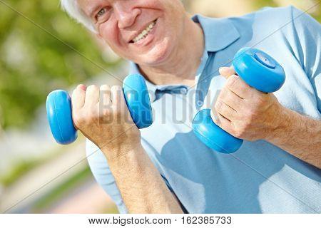 Senior man working out with blue dumbbells, focus on his hands