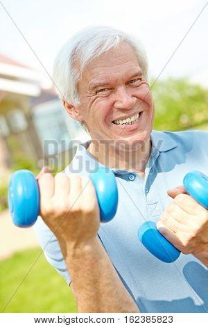 Senior man doing dumbbell exercise with effort