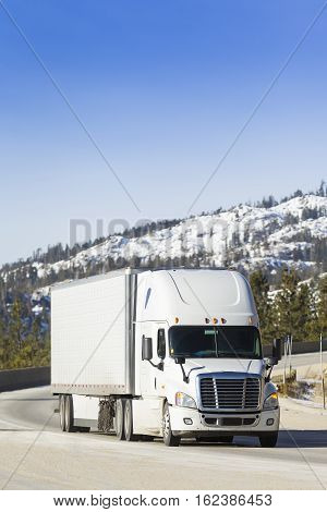 White Semi Truck 18-Wheeler on snowy mountain pass.