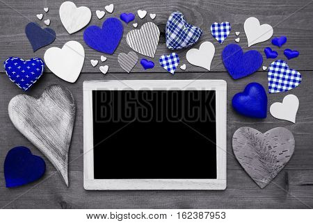 Chalkboard With Copy Space For Advertisement. Many Blue Textile Hearts. Wooden Background With Vintage, Rustic Or Retro Style. Black And White Image With Colored Hot Spots.