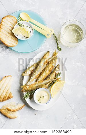 Fresh sea fish deep fried smelt on marble background with slices of lemon, salt, sauce and beverage glass. Top