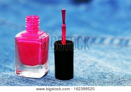 pink nail lacquer on jeans background macro