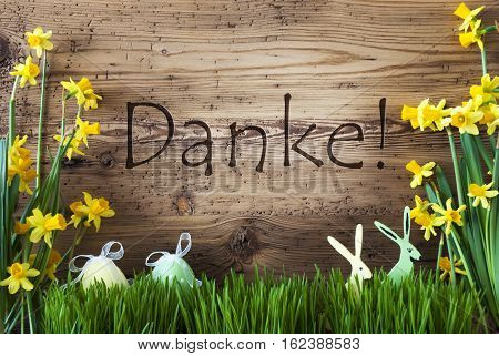 Wooden Background With German Text Danke Means Thank You. Easter Decoration Like Easter Eggs And Easter Bunny. Yellow Spring Flower Narcisssus With Gras. Card For Seasons Greetings