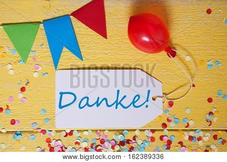 White Label With German Text Danke Means Thank You. Party Decoration Like Streamer, Confetti And Balloon. Flat Lay Or Top View. Yellow Wooden Background