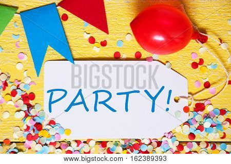 White Label With English Text Party. Close Up Of Party Decoration Like Streamer, Confetti And Balloon. Flat Lay Or Top View. Yellow Wooden Background