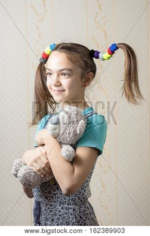 portrait of 11 year old girl with funny tails of rubber bands hugging teddy bear