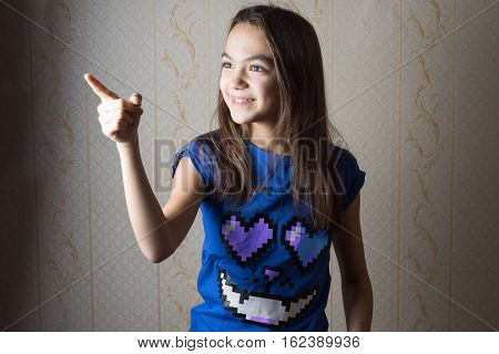 smiling 11 year old girl pointing her finger sideways