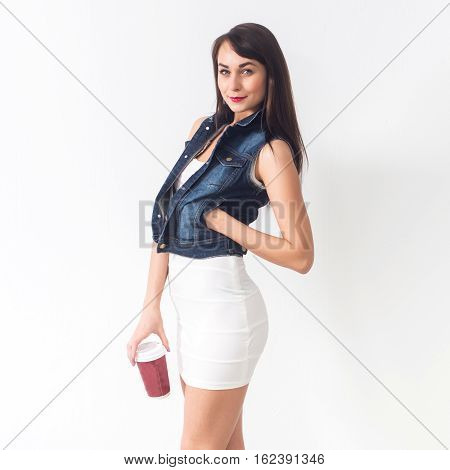 Beautiful brunette posing in casual stylish clothes on white background, holding red cup of take-away coffee, looking down, not isolated