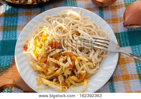 A Plate Of Spaghetti And Sauerkraut On A Checkered Towel  Тарелка со спагетти и тушеной капустой на