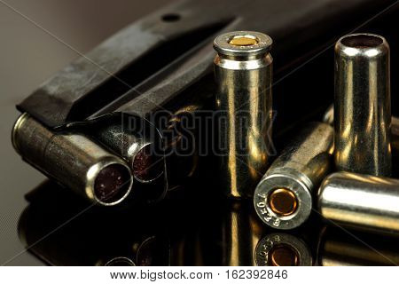 The loaded holder for the gun and cartridges against a dark background