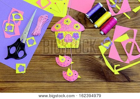 Homemade bright house with flowers and birds made of felt. Beautiful wall decor, sewing materials and tools on wooden table. Fun sewing craft concept. Simple spring or summer crafts for kids. Top view