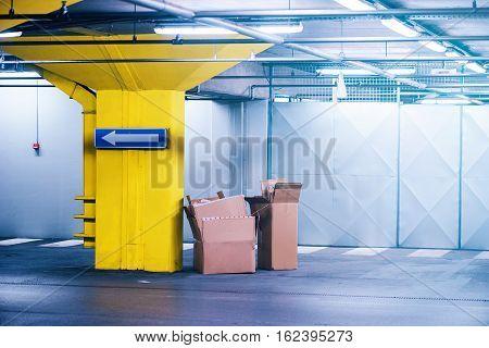 Empty cardboard boxes in underground garage parking lot urban exploration