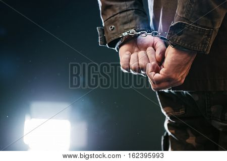 Handcuffed soldier arrested male army officer in dark prison cell