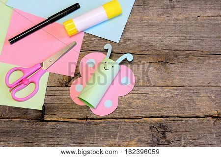 Pretty paper butterfly, scissors, marker, glue stick, colorful paper sheets on a wooden table. Creative paper crafts for children of all ages. Seasonal easy project for kids