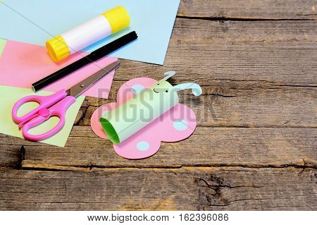 Nice paper butterfly, scissors, marker, glue stick, colorful paper sheets on background with copy space for text. Idea for kids arts and crafts activities in kindergarten, at home, at summer camp