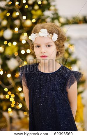 Portrait of the girl of younger school age against the background of the Christmas tree. The girl is dressed in a beautiful dark dress. On the head of her a wreath. The girl looks in the camera.