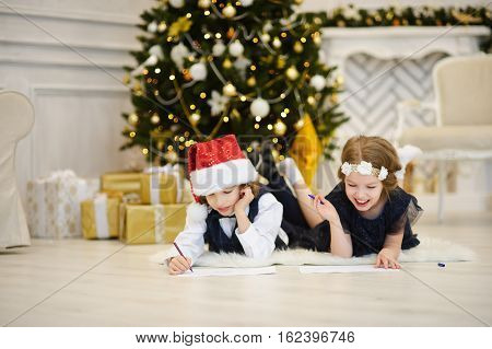 Children write letters to Santa Claus. To children it is cheerful. Little boy and girl lie on a floor near Christmas tree. House is festively decorated. Under Christmas tree there are a lot of gifts.