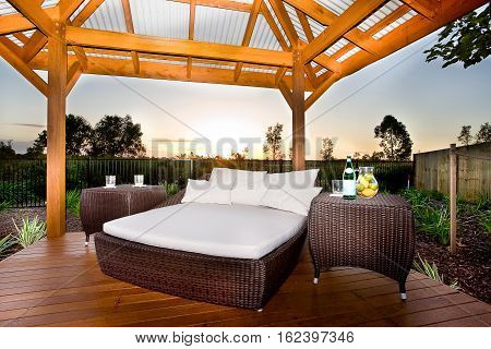 Place is made by wooden floor and pillars that holding a wooden beams in the roof There is a bed with white mattress and pillows and two tables made in rattan or similar material all prepared at the sundown