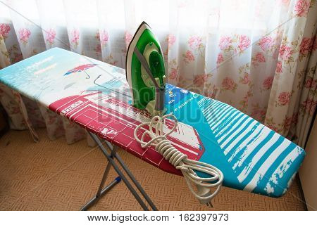Iron on ironing board with colored templates. Homelike atmosphere.