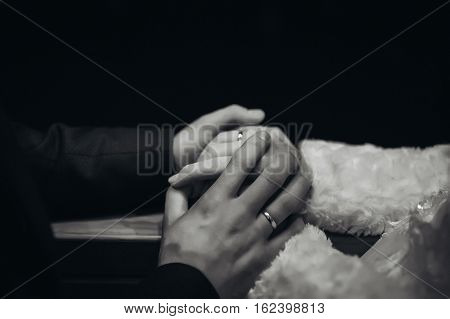 Romantic wedding scene the groom is gently holding the bride's hands, black and white image
