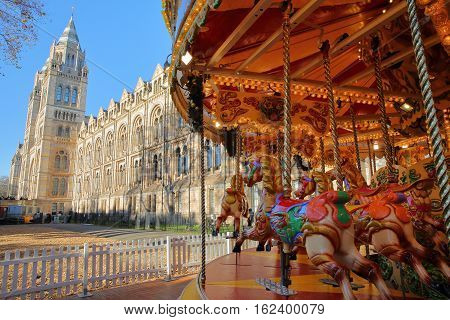 LONDON, UK - NOVEMBER 28, 2016: The Natural history museum in Winter with a Christmas children's carousel in the foreground
