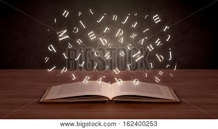 Glowing white alphabet letters coming out of an open book