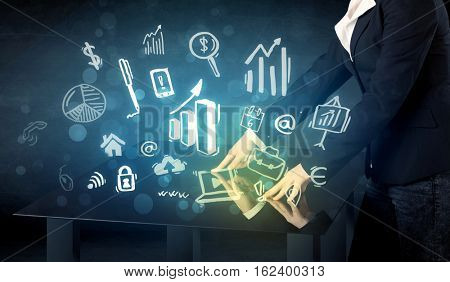 Man touching technology smart table with business icons and symbols