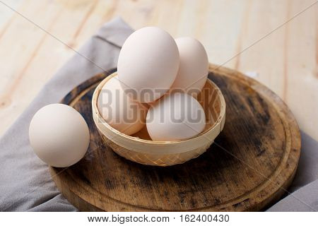 Egg in basket on cutting board on table