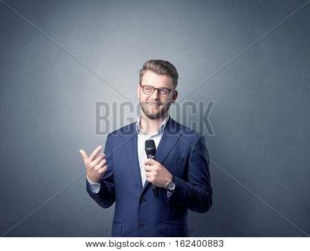 Businessman speaking into microphone with blue background