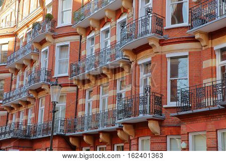 LONDON, UK - NOVEMBER 28, 2016: Red brick Victorian houses facades in the borough of Kensington and Chelsea with wrought iron railing
