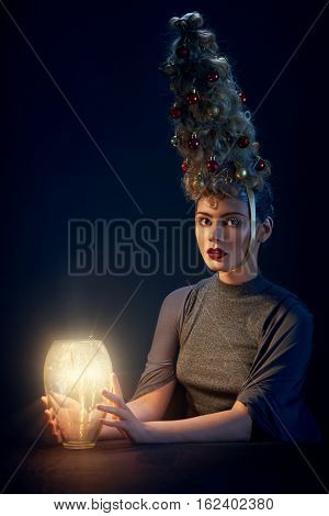 The beautiful woman with Christmas tree hairstyle and snow on eyelashes hold a sparkler