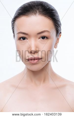 Facial emotions. Peaceful pleasant young woman smiling and expressing peacefulness while standing isolated in white background