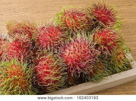 Fresh Fruits Fresh Ripe and Sweet Refreshing Rambutan Served on A Wooden Tray.