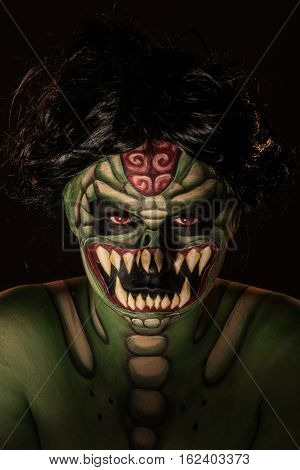 Professional body art of scary green monster snake with grin and red eyes