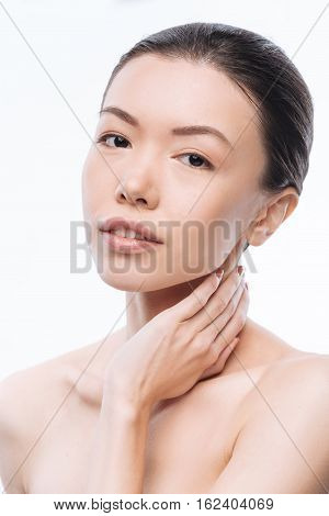 Charm in every motion. Charming feminine young Korean woman touching her neck and expressing elegance while standing isolated in white background