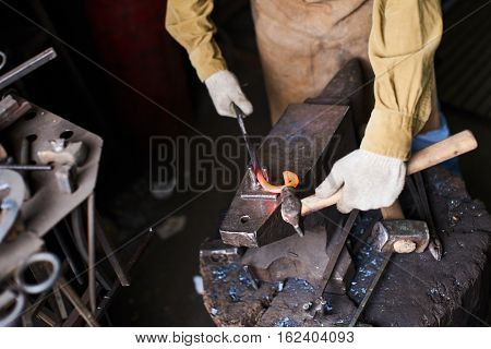 Male hands in the production process of metal products handmade on the anvil