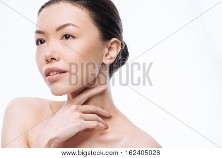 Beauty in details. Inspired delighted young Korean woman looking at the distance and expressing elegance while standing isolated in white background and touching her skin