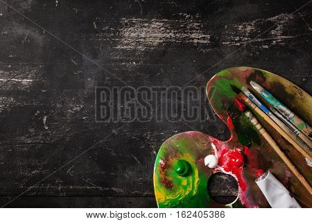 Palette with brushes on a black table top view