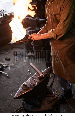 The hands heats the gas burner before working in the workshop