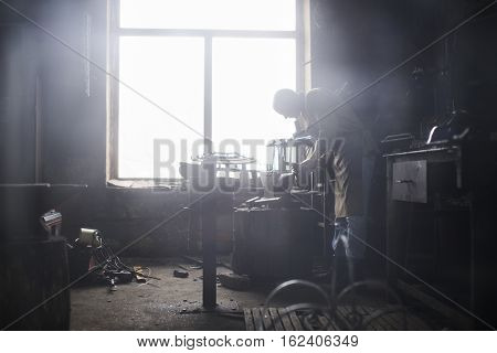 The blacksmith in the production of Handicrafts made of metal on the anvil in the workshop
